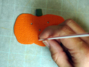 Poking holes in pumpkin with straw